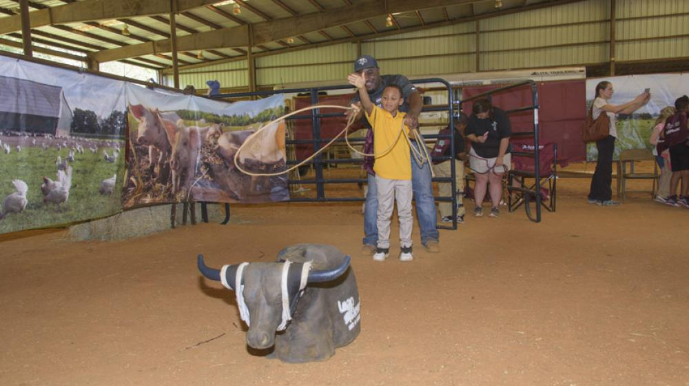 A young boy throws a rope toward a fake bull with the help of an older man standing behind him.