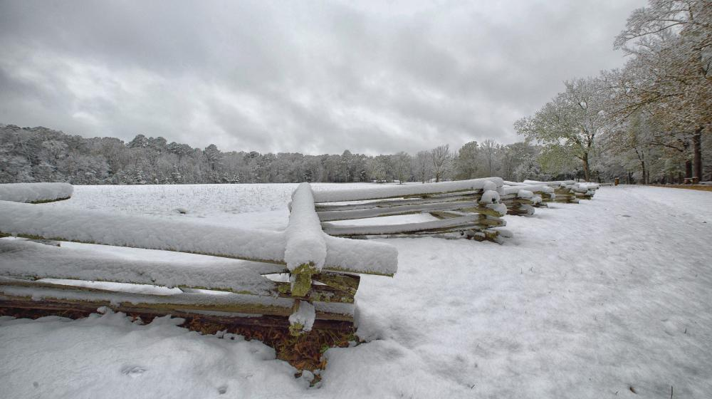 snow covers a fence and field in south Mississippi.