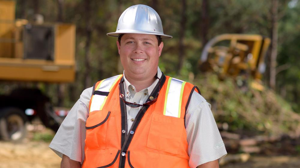 A young man with a metal construction hat and bright orange vest stands in front of his work site with his hands tucked into his blue jeans.