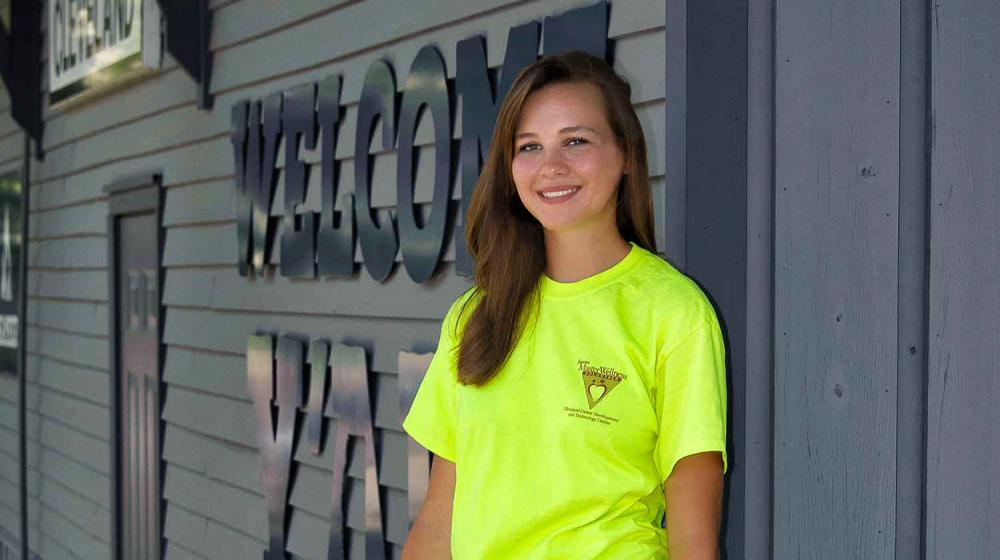 A teen with brown hair and wearing a green Junior Master Wellness Volunteer T-shirt stands in front of the Cleveland, Mississippi, Welcome Center.