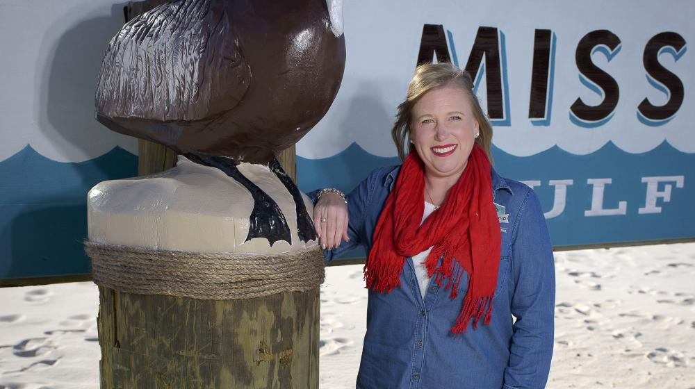 """A smiling woman with blonde hair, a red scarf, a denim shirt, and black pants rests her arm on the side of a """"Welcome to the Mississippi Gulf"""" sign."""