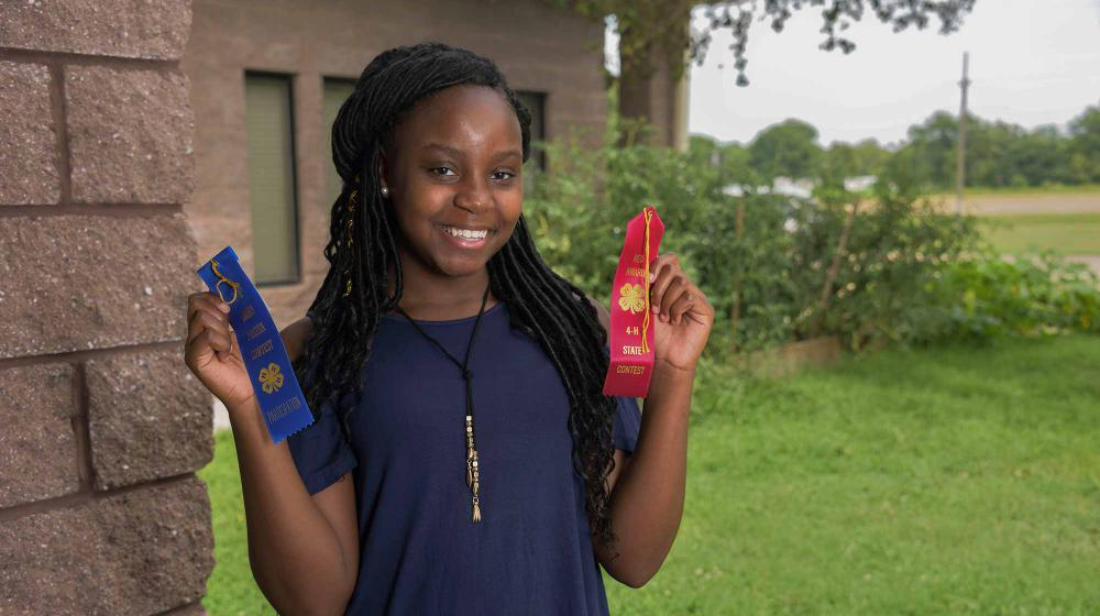 A teen girl wearing a blue shirt stands next to the corner of a brick wall and in front of green bushes. She holds a blue ribbon in her right hand and a red ribbon in her left.