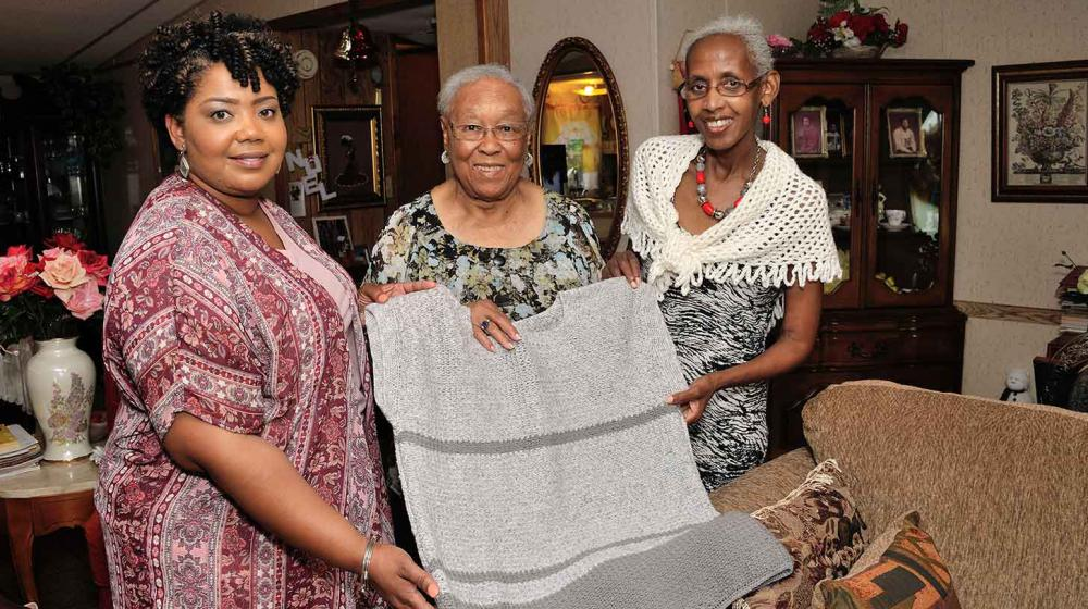 : On the left, a younger woman wearing a patterned pink shirt holds one side of a crocheted grey shirt shirt. In the middle, and older woman smiles. On the right, another older woman with grey hair and a crocheted piece of clothing smiles and holds the shirt.