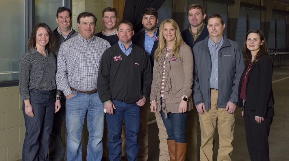 Ten adults, including 3 women and 7 men, stand smiling in front of a Mississippi Farmers' Market banner.