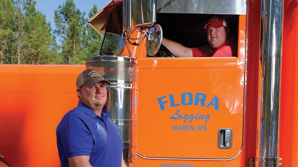 A man in a blue shirt stands in front of an orange semi-truck with another man in the driver seat.