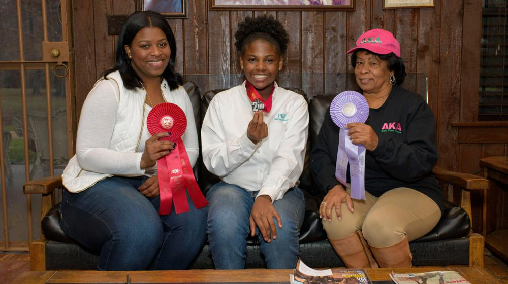 A young female dressed in a white polo and blue jeans smiles and holds up the second-place ribbon around her neck. On the left is an adult woman dressed in a white sheer top with a white vest and blue jeans and is holding a bigger red ribbon. On the right is an older woman wearing a pink AKA hat and a black long-sleeved AKA T-shirt with brown slacks, and she holds up a purple ribbon.