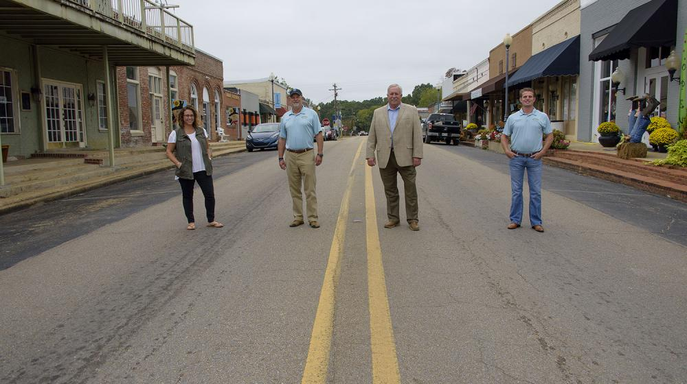 Four people stand on Main Street in Saltillo, MS.