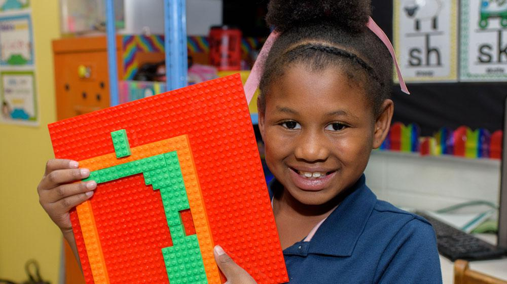 A young girl smiles and holds up a Lego creation.