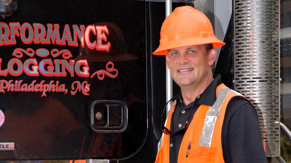 A man wearing a bright orange construction vest and hard hat stands in front of a logging machine.