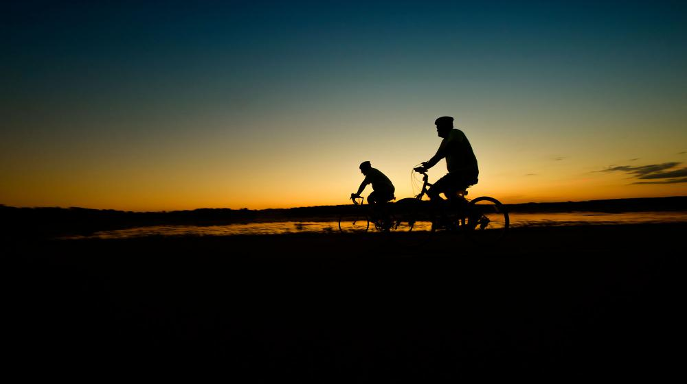The silhouettes of two cyclists are seen in front of a blue and yellow sunrise that reflects on a lake below.