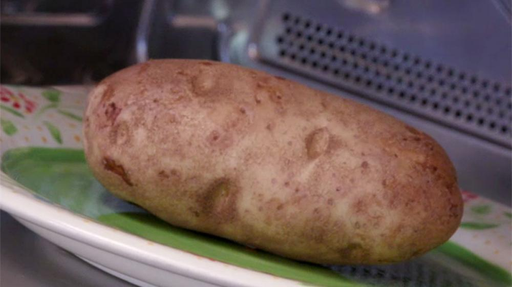 A close-up of a large brown Russet potato on a green plate with a white rim inside a microwave oven.