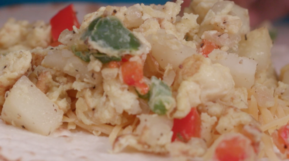 A mixture of diced onions, green and red bell peppers, scrambled eggs, and shredded cheese on a flour tortilla.
