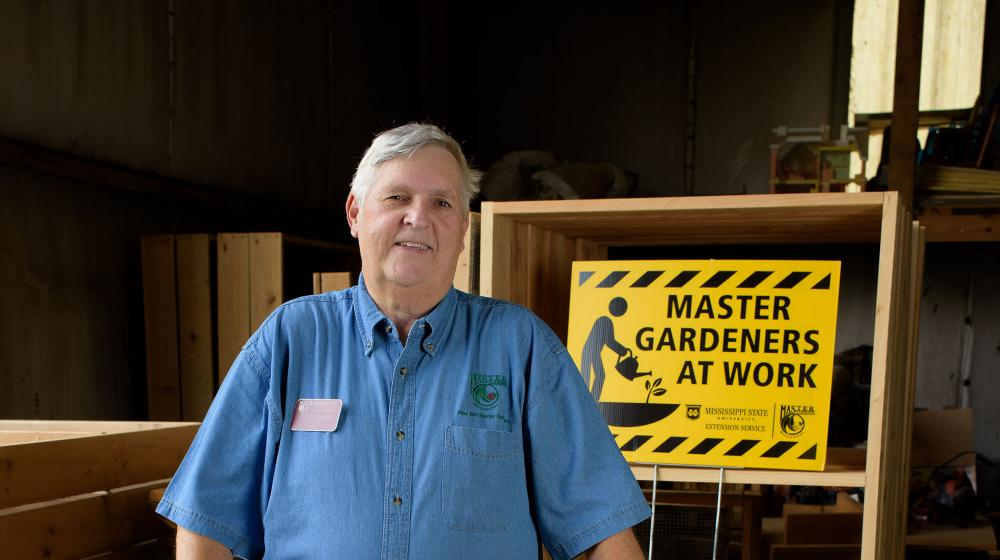 Paul Cavanaugh standing in front of a sign that reads Master Gardeners at Work.
