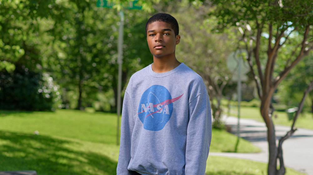 A young boy wearing a NASA sweatshirt stands on a sidewalk holding a camera by his side.