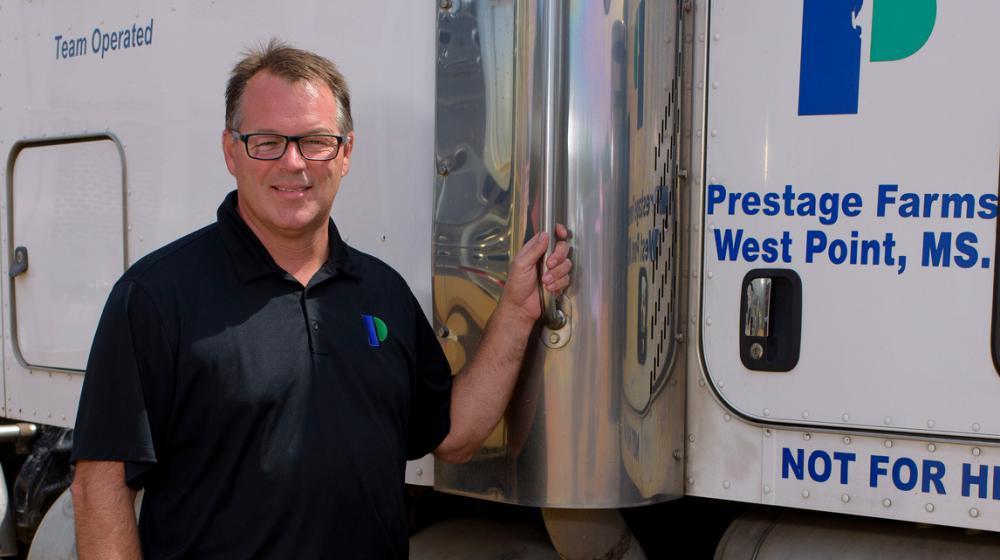 A man stands next to an 18-wheeler truck.