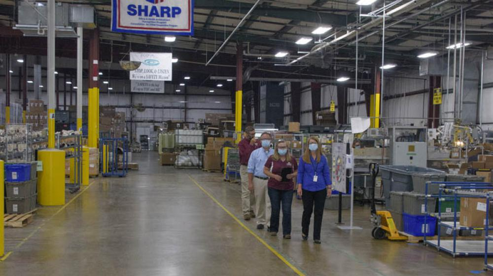 A line of four people walking in a room full of machinery and boxes.