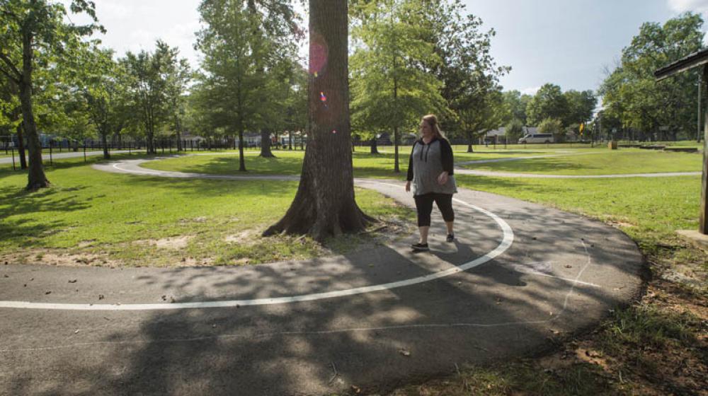 A woman walking on a sidewalk curved around a tall tree.