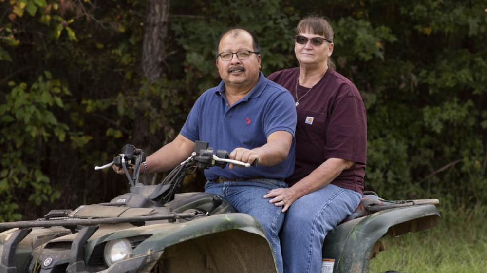 A man wearing a blue shirt and a woman wearing a maroon shirt sitting on a four-wheeler in tall green grass in front of dark green trees.