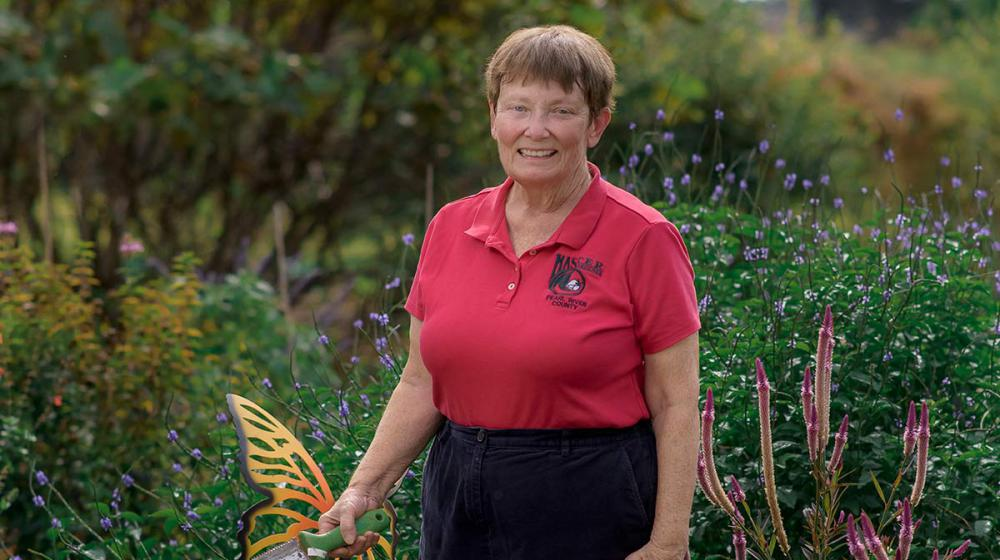 A woman wearing a red collared shirt standing in tall green grass and flowers. She holds a shovel in her right hand, which rests in front of a metal butterfly garden decoration.