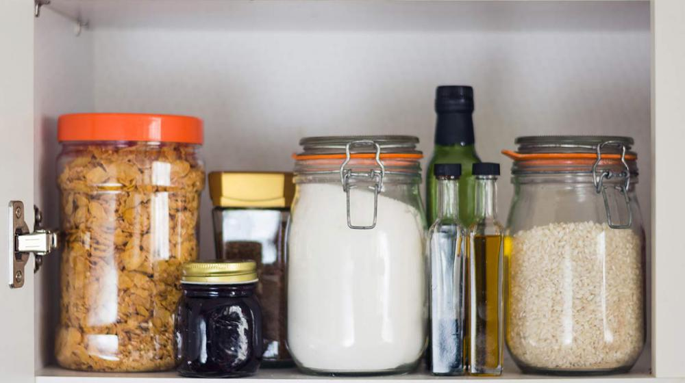 Airtight jars of cereal, rice and flour sit in a cupboard.