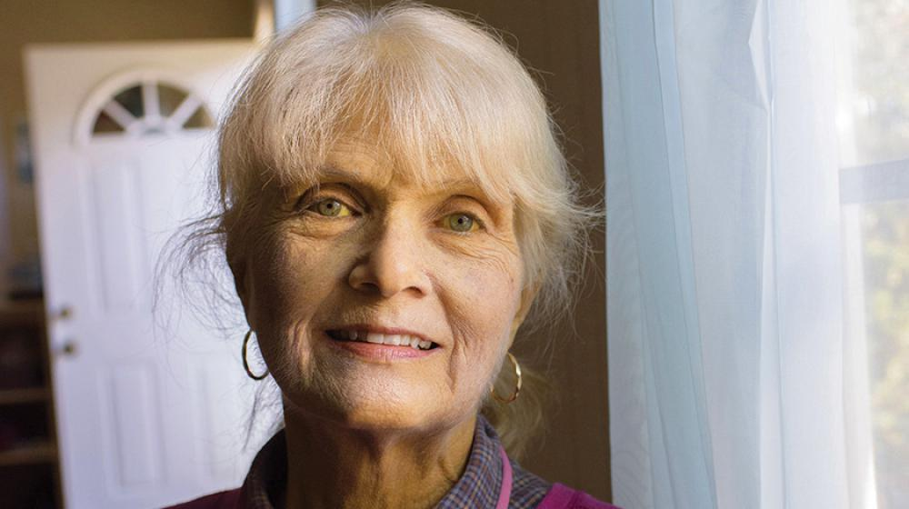 An smiling elderly woman stands next to a window.