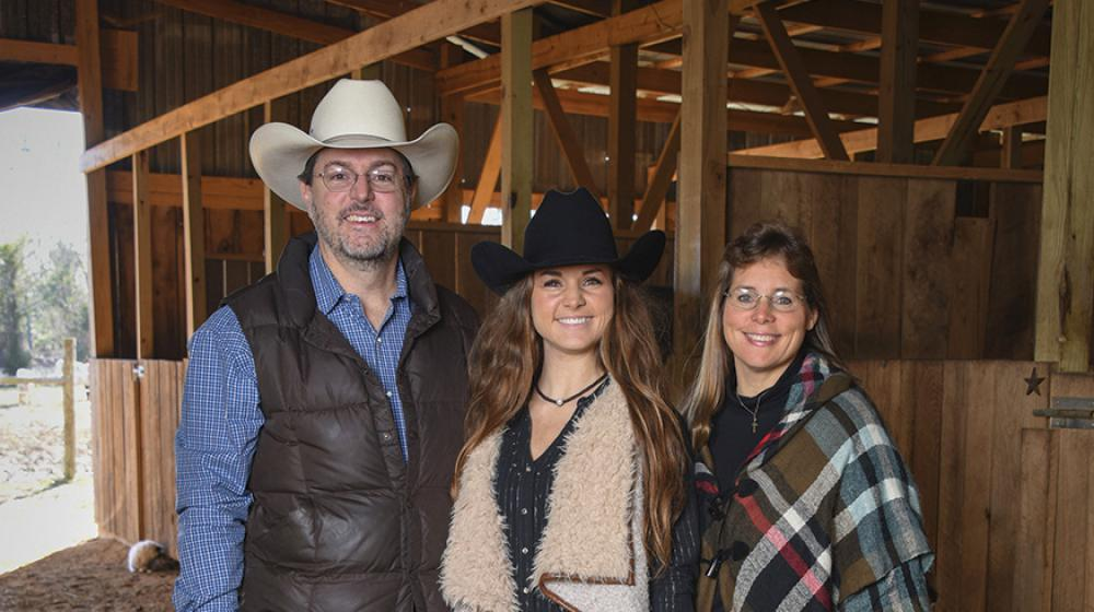 A teenage girl wearing a cowboy hat stand between her mom and dad, also wearing a cowboy hat, in a stable.