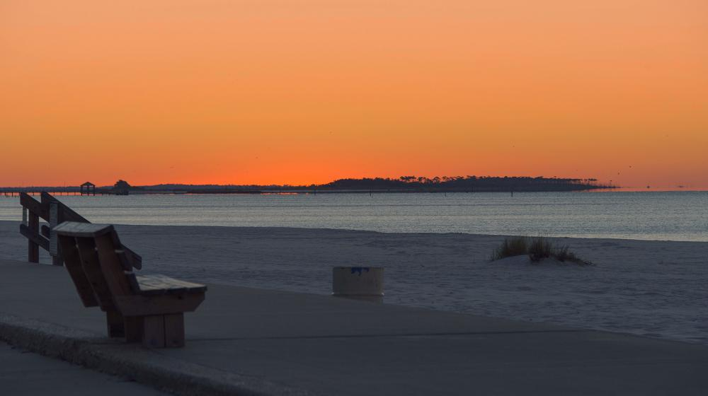 An orange sunset on Biloxi beach with the Gulf of Mexico in the background.