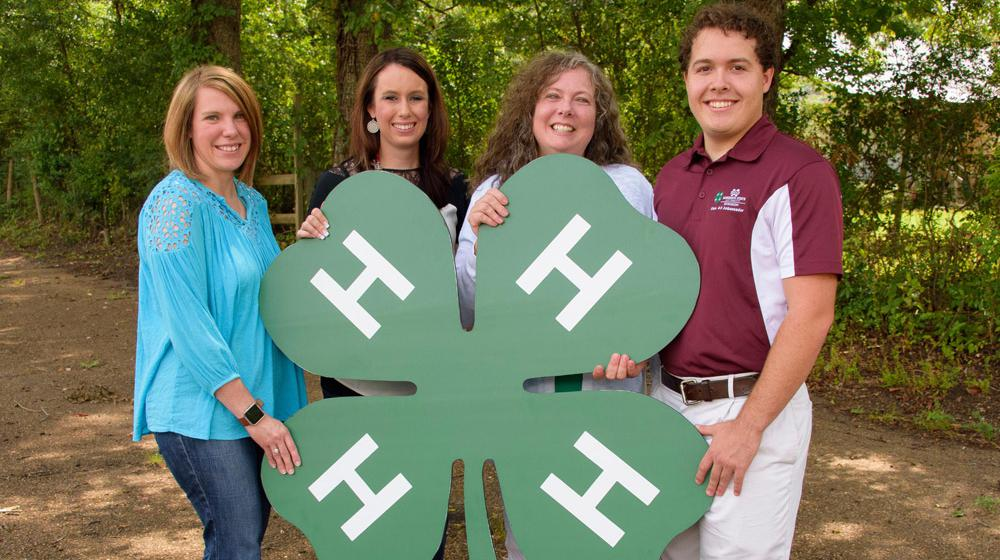 Three women and one man hold a large 4-H clover