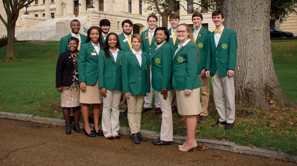 A group of high school girls and boys wearing khaki bottoms and green 4-H blazers stand in a group in front of the state capitol building.