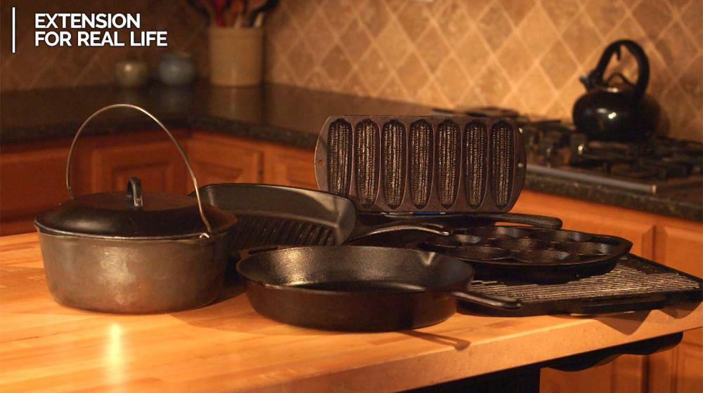 A grouping of various kinds of cast-iron cookware sit on a kitchen counter.
