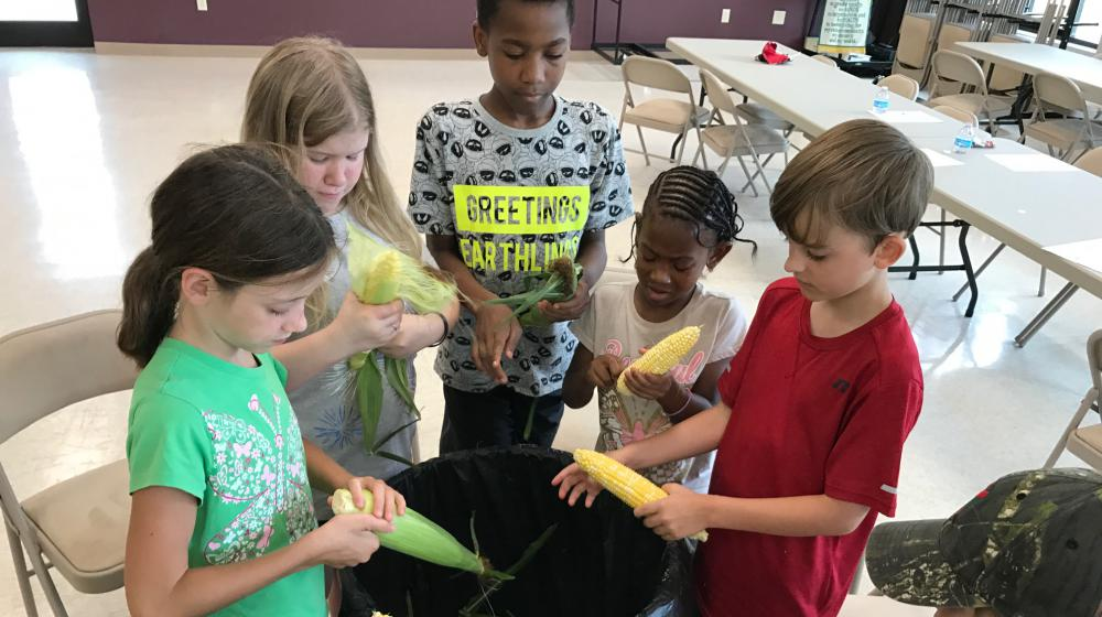 Children stand around a large garbage can while they shuck the husks and silks from ears of corn.