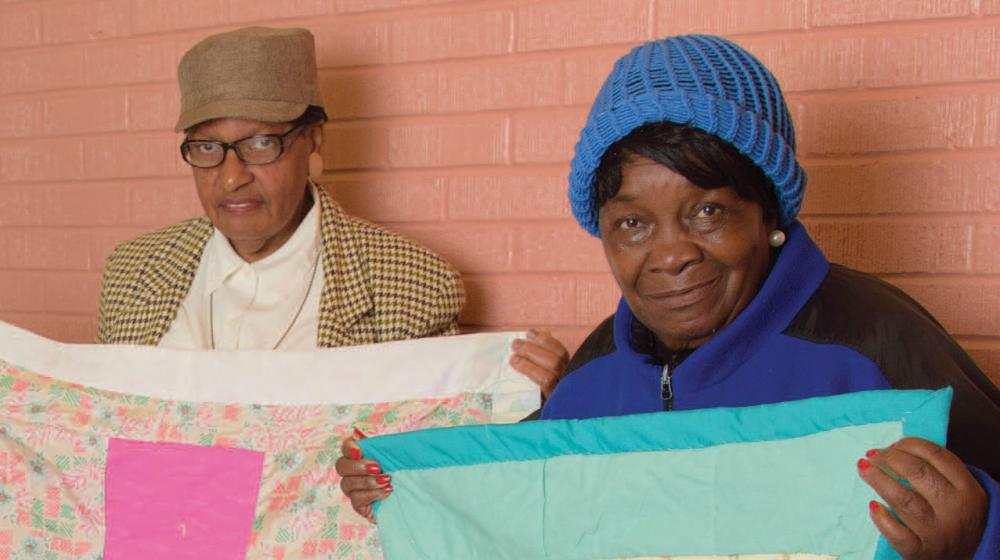 2 women hold up quilts.