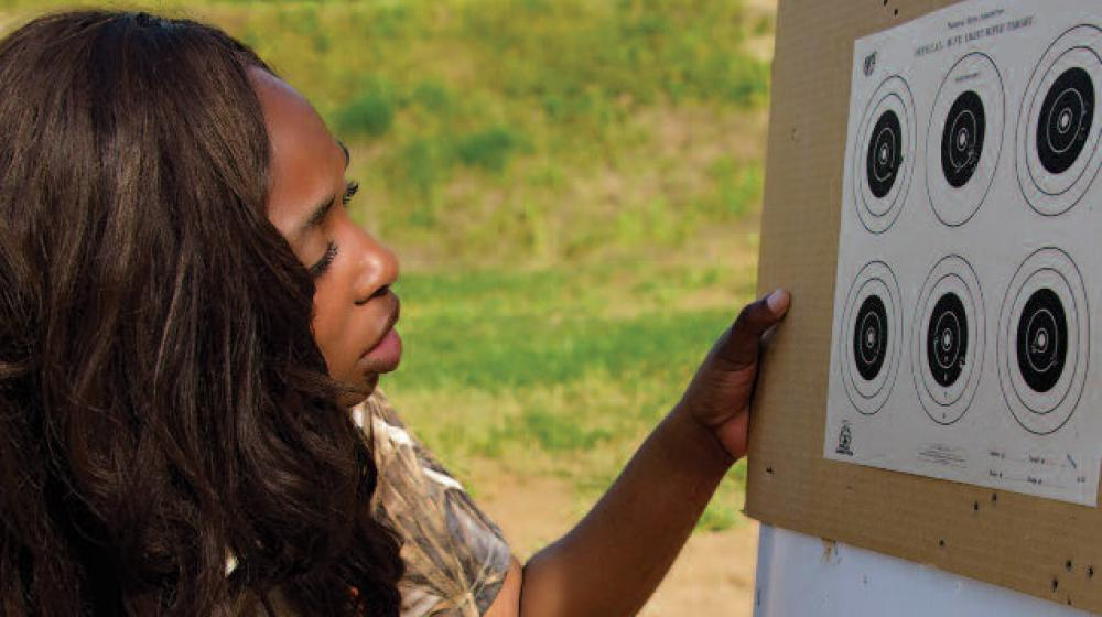 A young woman kneels down next to a board with targets.
