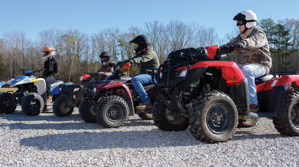Several men on ATVs lined up.