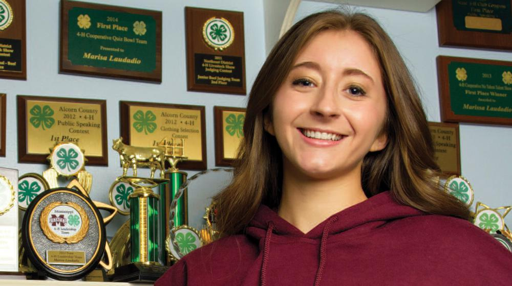 A girl wearing a maroon sweatshirt stands in front of a trophy display with her hands on her hips.