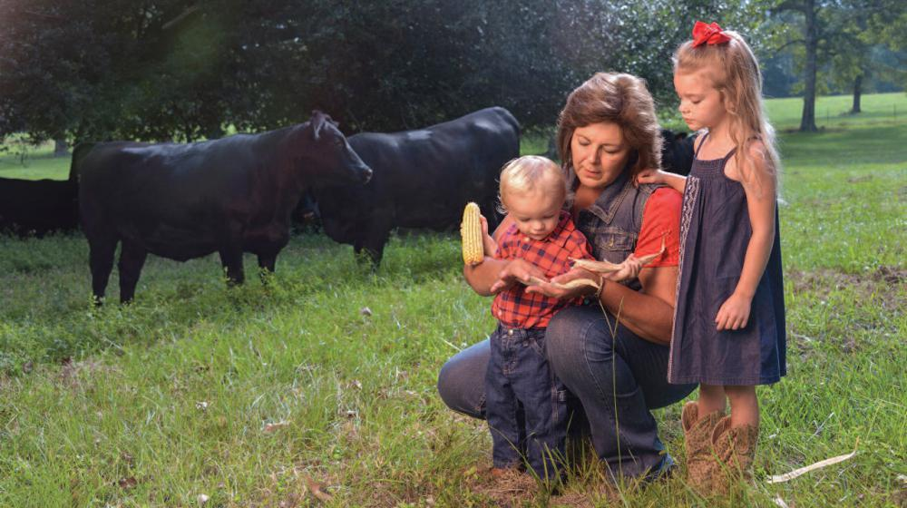 A woman and two small children in a field with black cows grazing behind them.