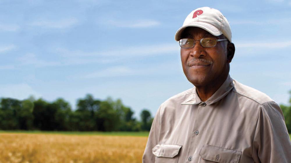 A man standing in a soybean field.