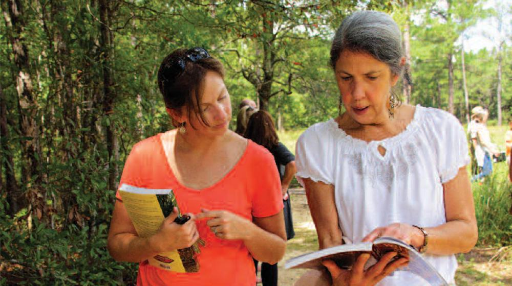 Two women walk and look at a book.