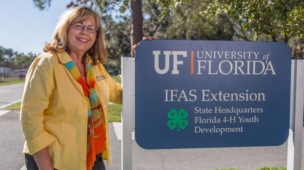 """A blonde woman with glasses, wearing a yellow shirt and a motley scarf, stands smiling on a sidewalk in front of trees beside a sign marking """"UF University IFAS Extension State Headquarters Florida 4-H Youth Development."""""""
