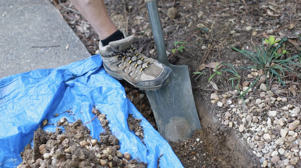 A person using their foot to shovel dirt from a trench.