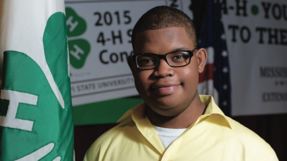A young boy next to a 4-H flag.