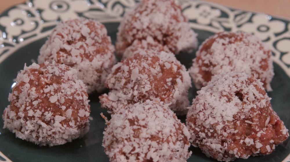 Strawberry cookie dough balls coated in coconut on a plate