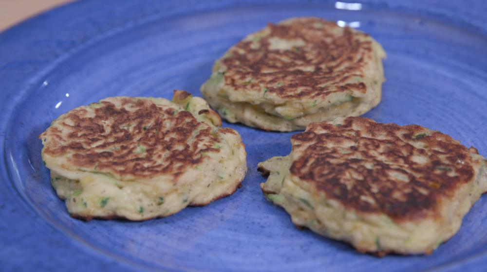 three zucchini fritters on a blue plate