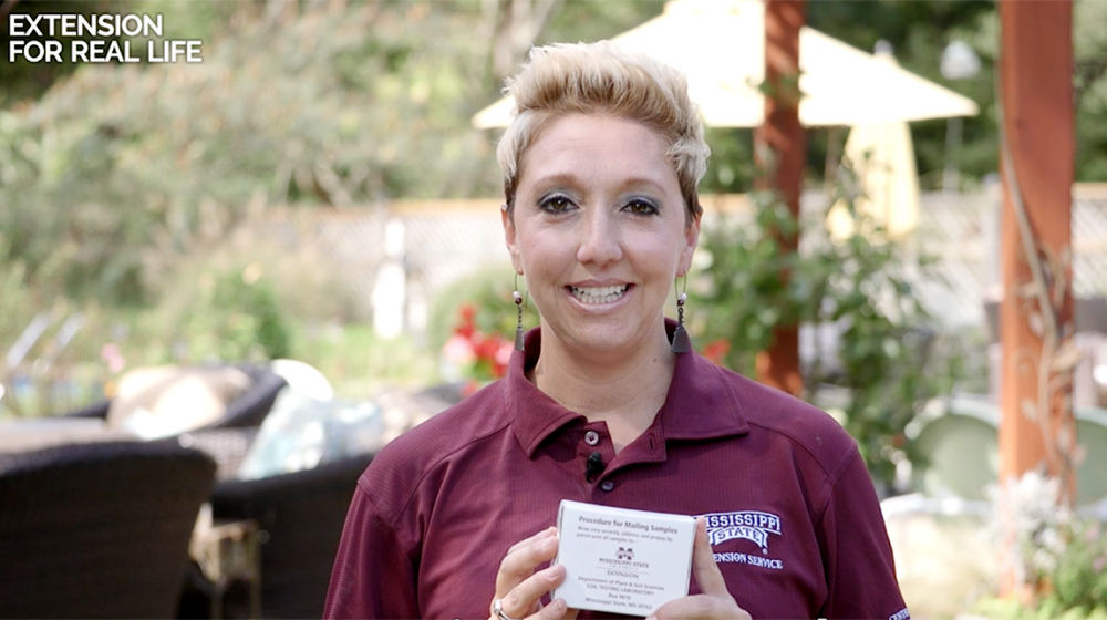MSU Extension agent Sandy Havard wears a maroon shirt and holds an Extension soil sample box.