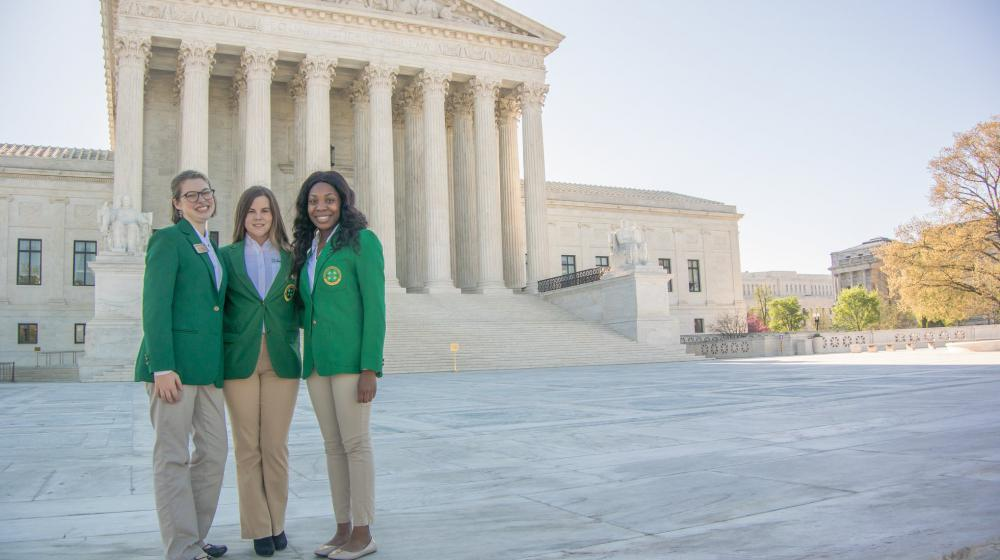 Three female teenagers wearing green blazers and khaki pants standing in front of the Supreme Court Building in Washington, D.C.