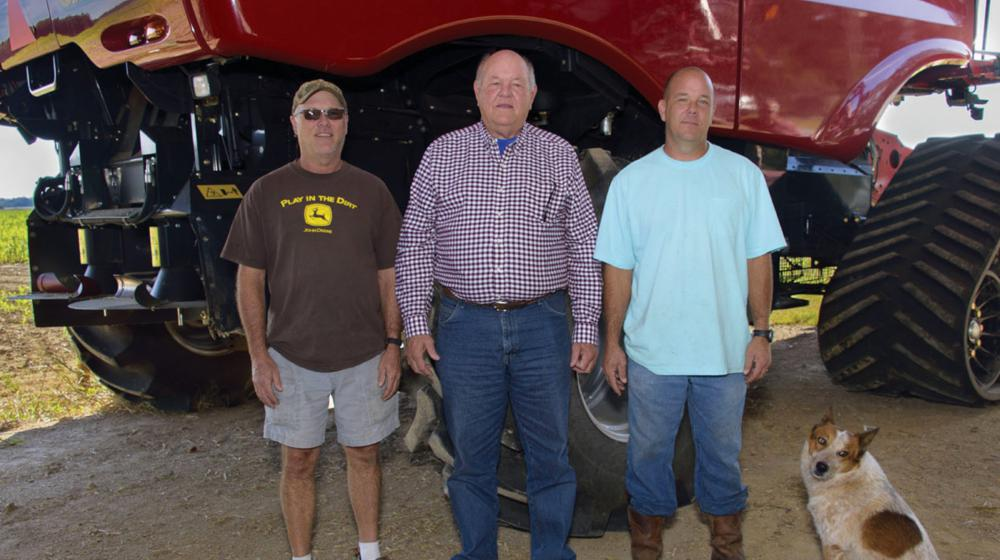 Three men and a dog stand in front of farm equipment.