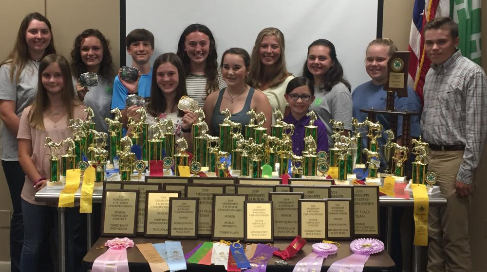 Twelve people stand behind a table covered in trophies, plaques, and different colored ribbons.