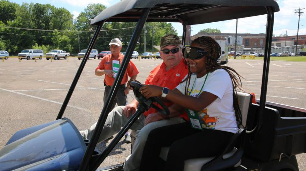 A young girl wearing goggles over her eyes sits next to an older man in a golf cart.