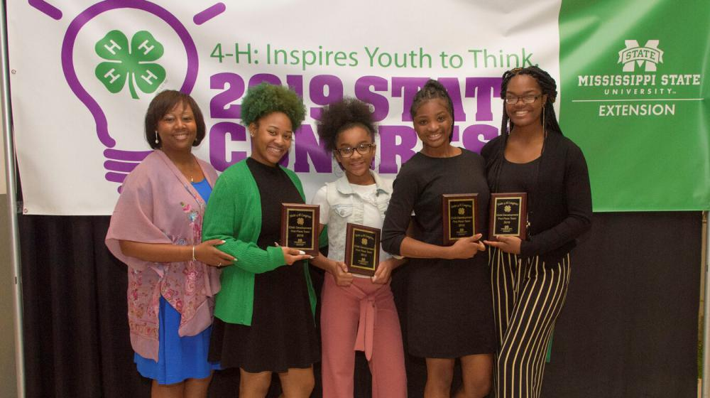 Four teenage girls hlding plaques and an older woman stand in front of a purple, white, and green 4-H poster.