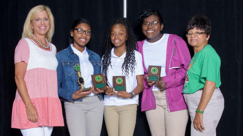 Three young girls holding 4-H plaques stand between two older women.